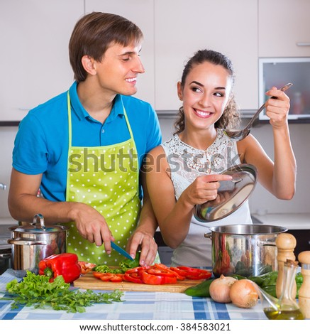 Smiling young man in apron helping wife to prepare healthy vegetarian dinner