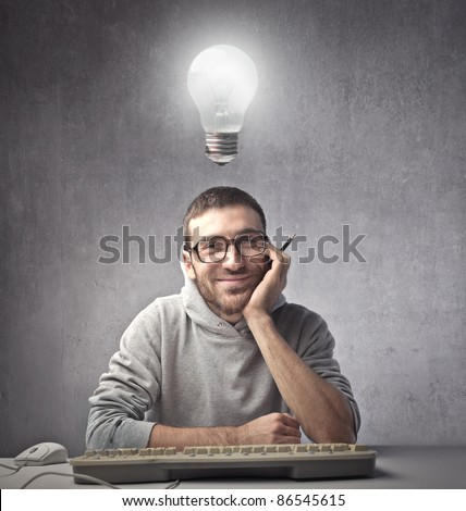 Smiling young man in front of a computer with light bulb over his head - stock photo