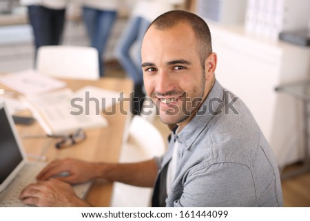 Smiling young man in office working on laptop - stock photo