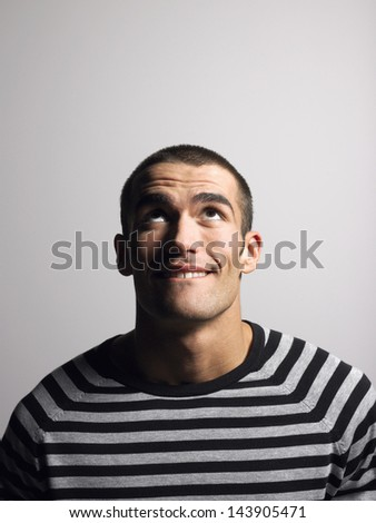 Smiling young man in striped tshirt looking up against gray background - stock photo