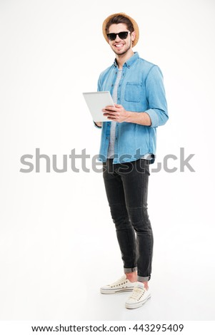 Smiling young man in sunglasses and hat holding and using tablet over white background - stock photo