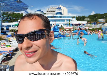 smiling young man in sunglasses in aquapark, wide angle - stock photo