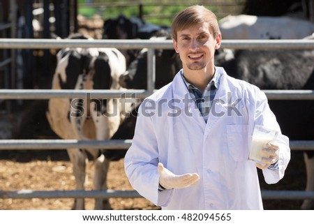 smiling young man in the white coat standing with cows and holding fresh milk