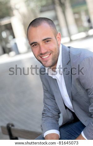 Smiling young man in town - stock photo