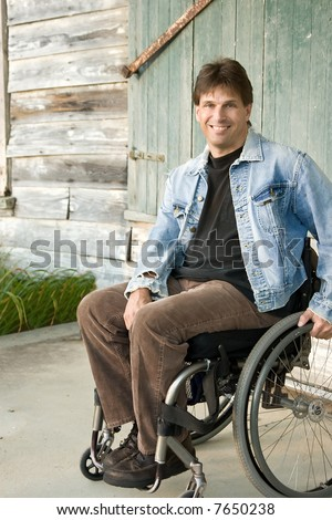 smiling young man in wheelchair - stock photo