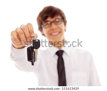 Smiling young man in white shirt and black tie holding out car keys. Isolated on white background, mask included focus on keys