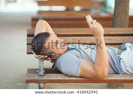 Smiling young man is resting on the park bench listening to music. He is wearing headphones and looking for his favorite music play list on his mobile phone.