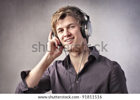 Smiling young man listening to music through headphones - stock photo