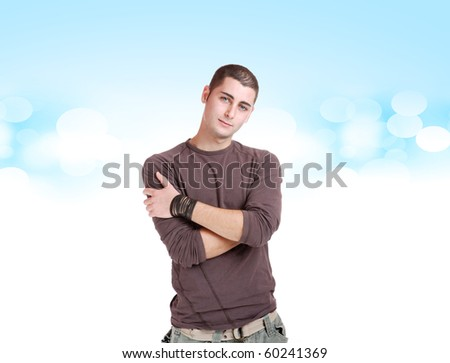Smiling young man looking at camera over blue background - stock photo