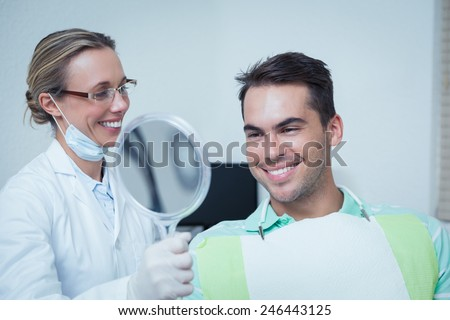 Smiling young man looking at mirror in the dentists chair - stock photo