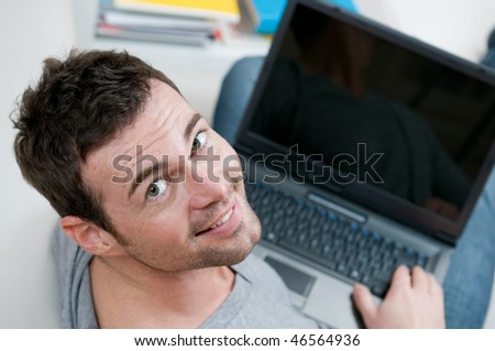 Smiling young man looking back at camera while working on laptop at home - stock photo