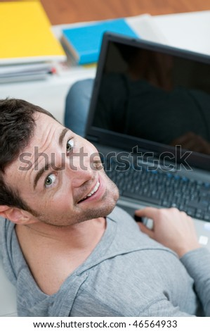Smiling young man looking back at camera while working on laptop at home with copy space