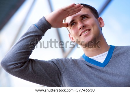 Smiling young man looking into future - stock photo