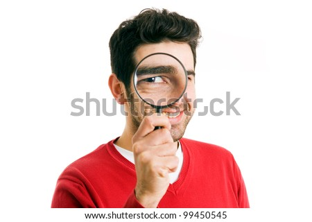 Smiling young man looking through magnifying glass, isolated on white