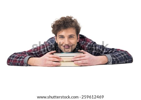 Smiling young man lying on the table with books - stock photo