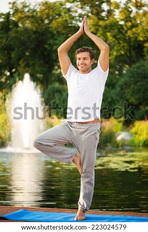 Smiling young man practicing yoga, doing tree pose. With a beautiful green scenery of park on background - stock photo