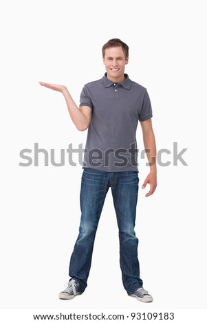 Smiling young man presenting with his palm up against a white background - stock photo