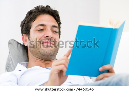 Smiling young man reading a novel book while relaxing on sofa - stock photo