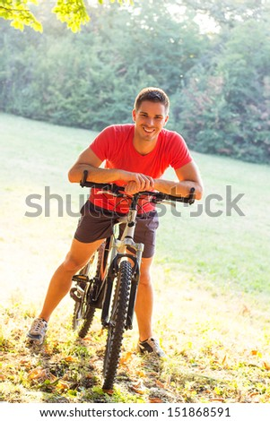 Smiling young man riding bicycle - stock photo