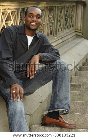 Smiling young man seated on ornate park steps.