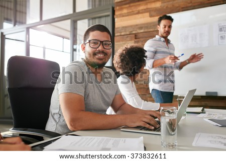 Smiling young man sitting at a business meeting with colleagues - stock photo
