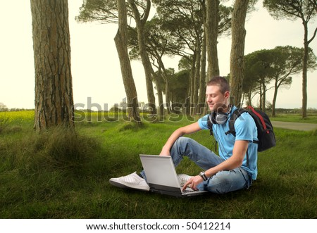 Smiling young man sitting in a forest and using a laptop - stock photo