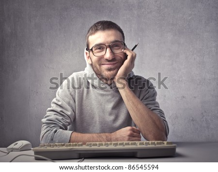 Smiling young man sitting in front of a computer keyboard - stock photo