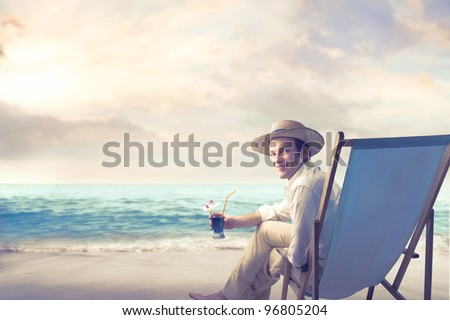 Smiling young man sitting on a deckchair and holding a cocktail at the seaside - stock photo