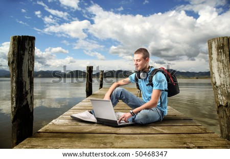Smiling young man sitting on a dock and using a laptop - stock photo