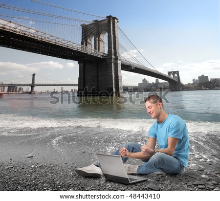 Smiling young man sitting on the bank of a river with a laptop on front of him and the Brooklyn Bridge on the background - stock photo