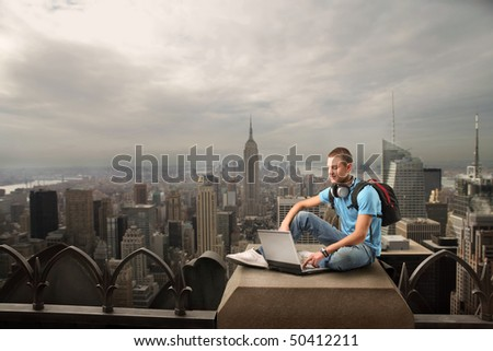 Smiling young man sitting on the top of a skyscraper and using a laptop - stock photo