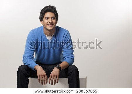 Smiling young man sitting over colored background - stock photo
