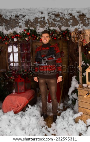 Smiling Young Man Standing at the House with Plenty Christmas Decors in Winter Fashion Outfit, with Ice Skates Hanging Around his Neck, While Looking at the Camera. - stock photo