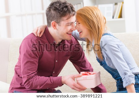 Smiling young man surprises his girlfriend with gift at home. Love concept - stock photo