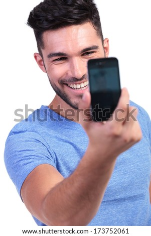 smiling young man taking his own picture with his smart phone on white background - stock photo