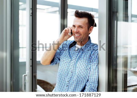Smiling young man talking on his mobile - stock photo