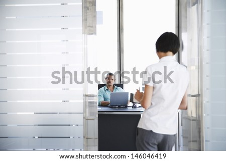 Smiling young man talking to woman standing in doorway at his office - stock photo