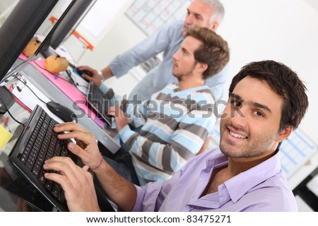 Smiling young man using a computer - stock photo