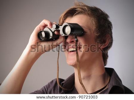 Smiling young man using binoculars - stock photo