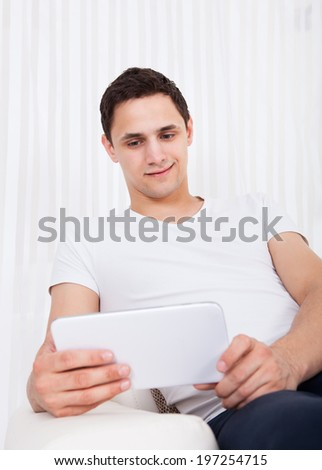Smiling young man using digital tablet in living room