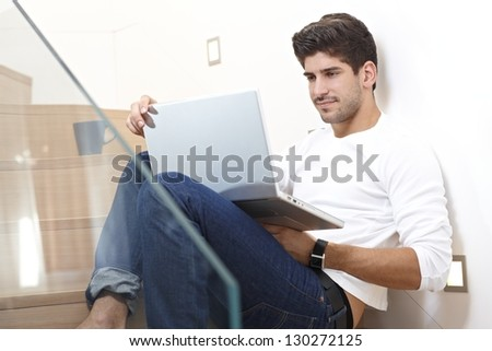 Smiling young man using laptop computer at home, sitting on stairs. - stock photo