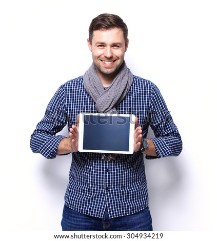 Smiling young man using tablet computer against a white background