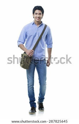 Smiling young man walking over white background - stock photo