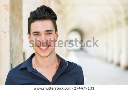 Smiling young man wearing black shirt looking at camera outdoor under arched cloister - stock photo