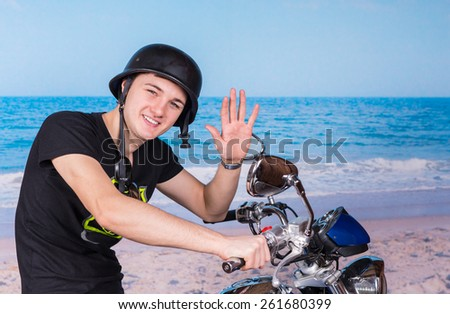 Smiling Young Man Wearing Helmet Sitting on Motorcycle at Beach and Waving to Camera - stock photo