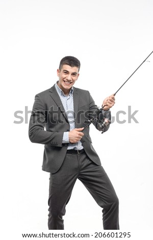 Smiling young man wearing nice suit catching something really great. Concept of comparison fishing and business. Isolated on white background
