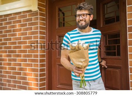 Smiling young man with bouquet of flowers is waiting for his girlfriend.
