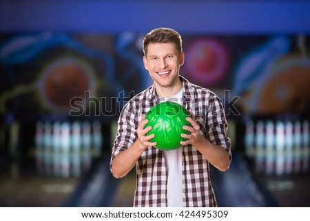 Smiling young man with bowling ball - stock photo