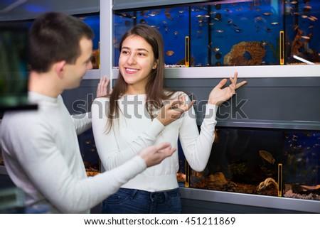 Smiling young man with brunette girlfriend choosing aquarium fish in aquarium - stock photo