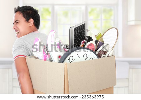 Smiling young man with cardboard box. moving day concept